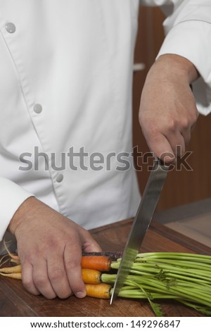 Midsection of male chef cutting carrots on wooden board in kitchen - stock photo