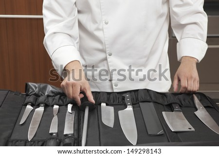 Midsection of male chef selecting knife sharpener out of full set in commercial kitchen - stock photo