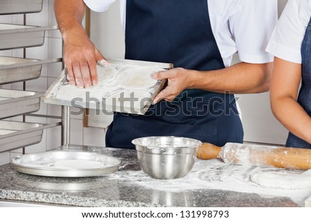 Midsection of male chef working in commercial kitchen - stock photo
