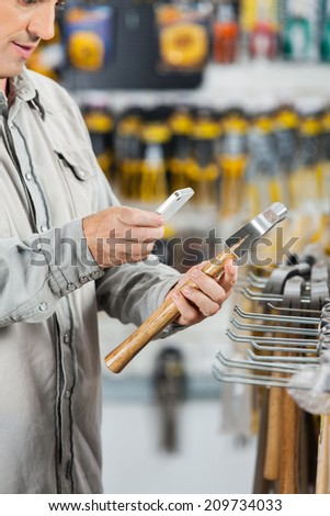 Midsection of male customer scanning hammer through mobilephone in hardware store - stock photo