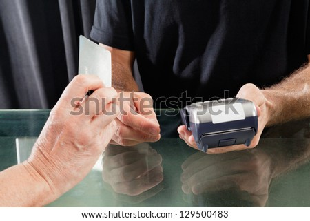 Midsection of male hairstylist accepting payment through credit card from female customer - stock photo