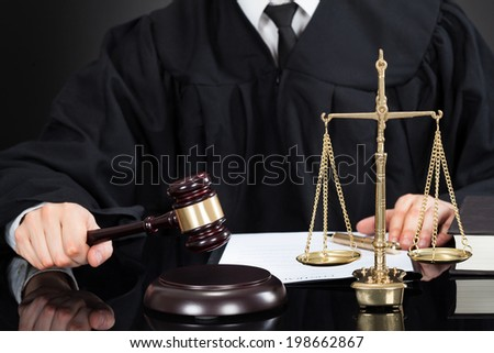 Midsection of male judge with mallet and weight scale at desk against black background - stock photo