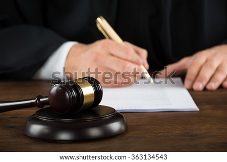 Midsection of male judge writing on legal documents at desk in courtroom - stock photo