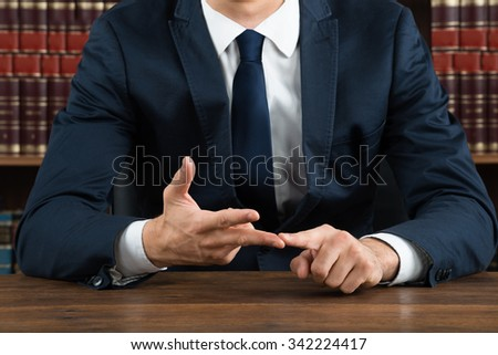 Midsection of male lawyer gesturing while sitting at desk in courtroom - stock photo