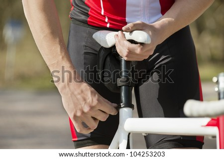 Midsection of man adjusting the seat of his bicycle - stock photo