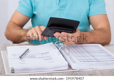Midsection of man calculating financial expenses at home - stock photo