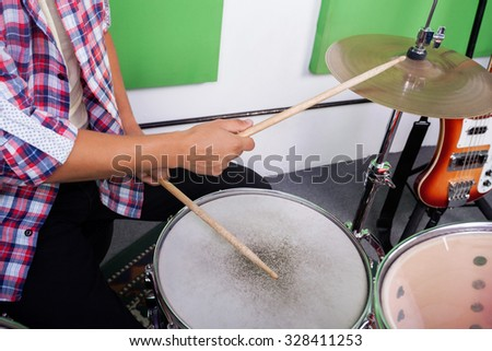 Midsection of man playing drums in recording studio - stock photo