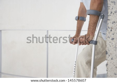 Midsection of man walking with crutches at home - stock photo