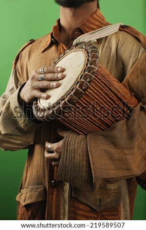 Midsection of man with drum - stock photo