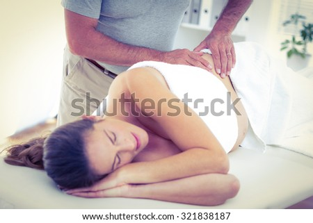 Midsection of masseur giving massage to woman sleeping on bed in spa - stock photo
