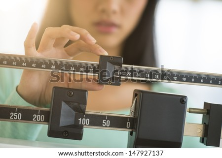 Midsection of mid adult Asian woman adjusting balance weight scale - stock photo