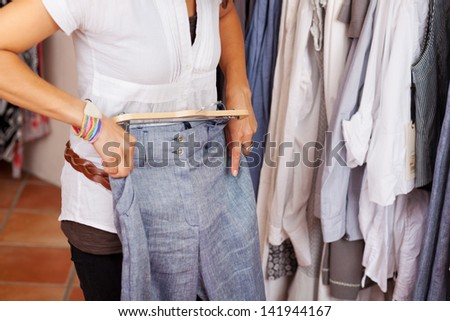 Midsection of mid adult woman trying blue trouser in clothing store - stock photo