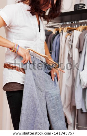 Midsection of mid adult woman trying trouser in clothing store - stock photo