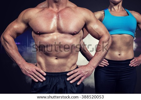 Midsection of muscular man and woman standing with hands on hip against smoke - stock photo