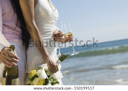 Midsection of newlywed couple with champagne bottle and flutes on beach - stock photo