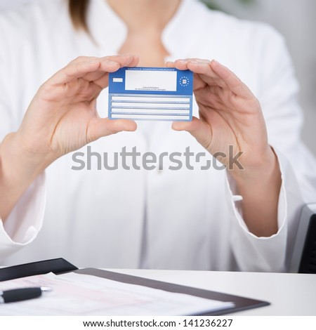 Midsection of receptionist showing medical card at counter in hospital - stock photo