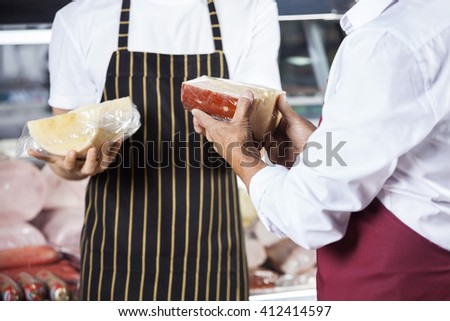 Midsection Of Salesmen Holding Fresh Cheese - stock photo