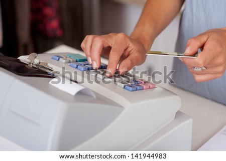 Midsection of saleswoman holding credit card while using cash desk at boutique counter - stock photo