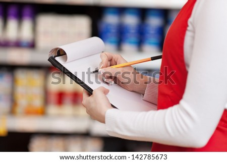Midsection of saleswoman writing on clipboard in grocery store - stock photo