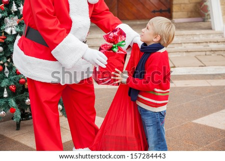 Midsection of Santa Claus giving gift to boy outside house - stock photo