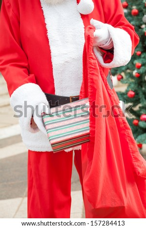 Midsection of Santa Claus putting present in bag outdoors - stock photo