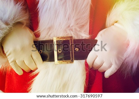 Midsection of Santa Claus with hands on stomach - stock photo