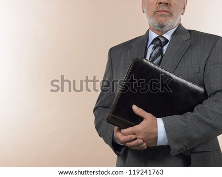 Midsection of senior businessman holding leather binder over colored background - stock photo