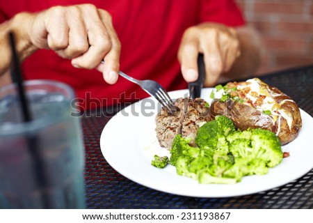 Midsection of senior man eating strip steak served with loaded baked potato and broccoli at restaurant table - stock photo