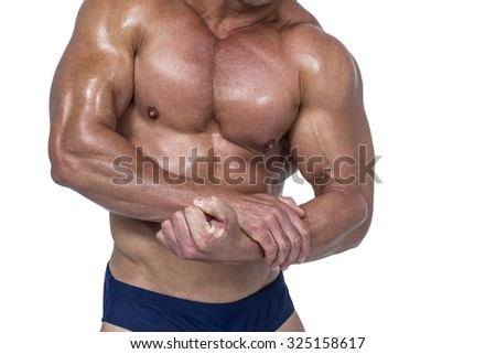 Midsection of shirtless man flexing muscles against white background - stock photo