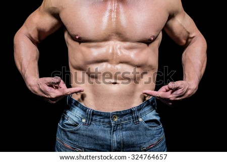 Midsection of shirtless man pointing at abs against black background - stock photo