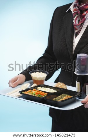 Midsection of stewardess holding tray with airplane food on blue background - stock photo