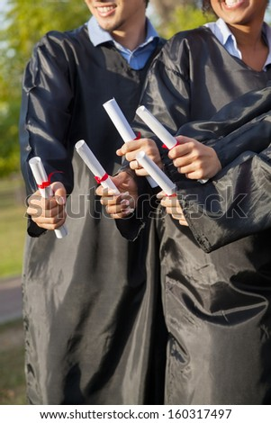 Midsection of students holding diplomas on graduation day in college - stock photo