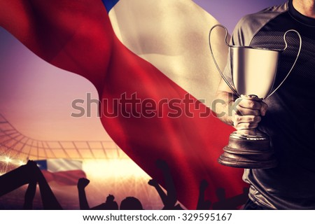 Midsection of successful rugby player holding trophy and ball against large football stadium under purple sky - stock photo