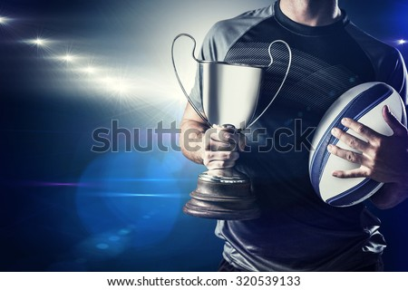 Midsection of successful rugby player holding trophy and ball against spotlights - stock photo