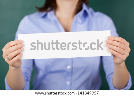 Midsection of teacher holding blank label against chalkboard - stock photo