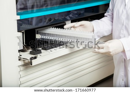 Midsection of technician placing samples in analyzer at laboratory - stock photo