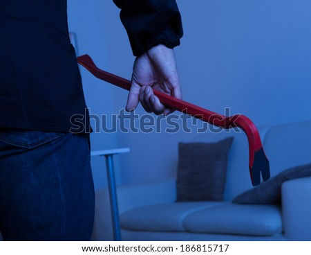 Midsection of thief holding crowbar in living room - stock photo