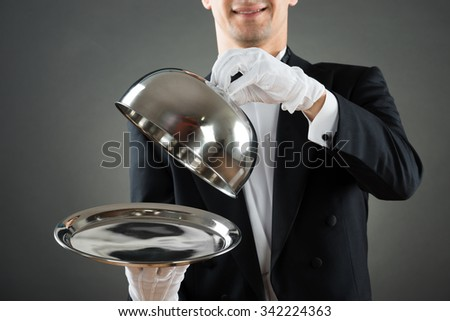 Midsection of waiter holding cloche over empty tray while standing against gray background - stock photo