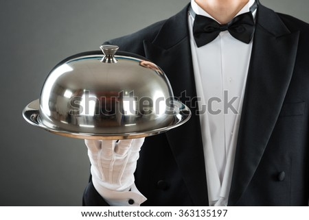 Midsection of waiter holding tray with cloche against gray background - stock photo