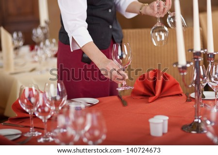 Midsection of waitress arranging wineglasses on table in restaurant - stock photo