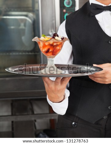 Midsection of waitress holding delicious dessert in commercial kitchen - stock photo