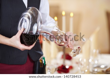 Midsection of waitress pouring red wine in wineglass - stock photo