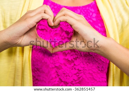 Midsection of woman with heart shape made from fingers - stock photo