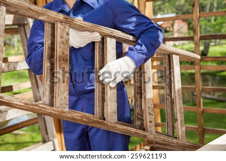 Midsection of worker carrying ladder at construction site - stock photo