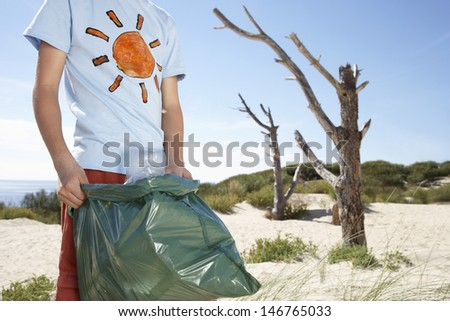 Midsection of young boy carrying plastic bag filled with garbage on beach - stock photo