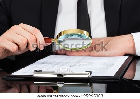 Midsection of young businessman analyzing document with magnifying glass at desk - stock photo