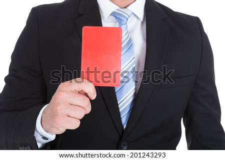 Midsection of young businessman showing red card over white background - stock photo