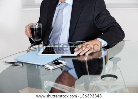 Midsection of young businessman with coffee cup using digital tablet at desk in office - stock photo
