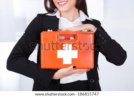 Midsection of young businesswoman holding first aid box in office - stock photo