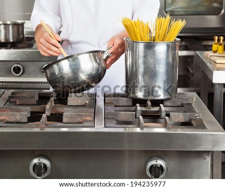 Midsection of young chef cooking spaghetti in commercial kitchen - stock photo